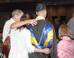 Family hugging student in regalia.