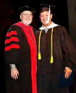 Graduate stands next to president Randy Roberts while holding his diploma.