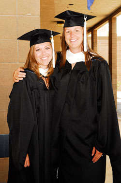 Two graduates smile while posing for a photograph.