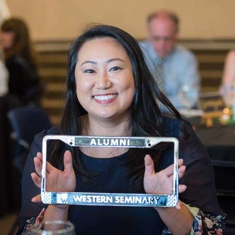 "Graduate holding a frame that says ""Alumni""."